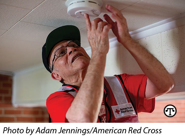 A Red Cross volunteer installs a free smoke alarm    through the Home Fire Campaign.