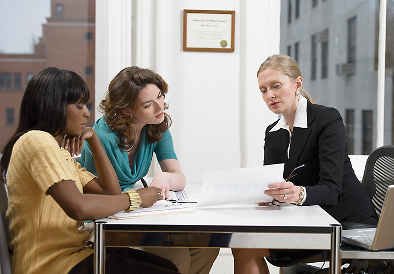 Doctor Explaining a Document to Two Women Sitting at Her Desk in Her Clinic